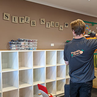 cleaner spraying storage space in childcare centre hobart